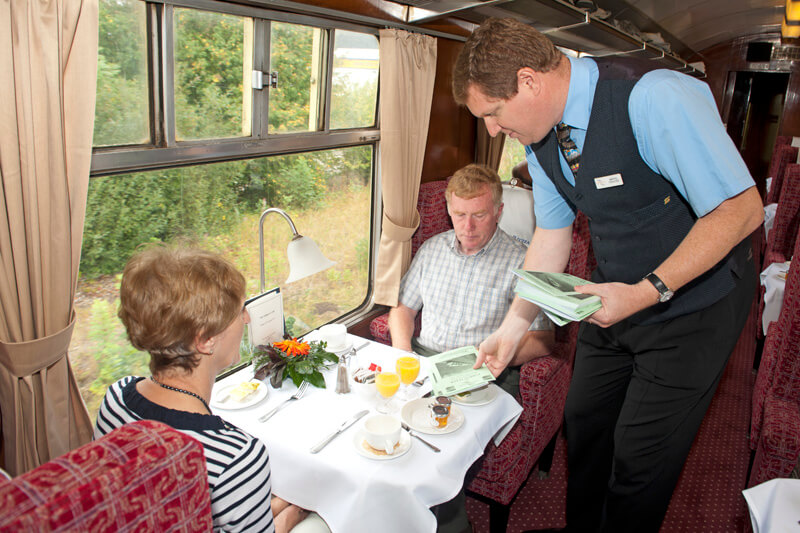 A Pathfinder Tours Steward welcoming passengers to the train